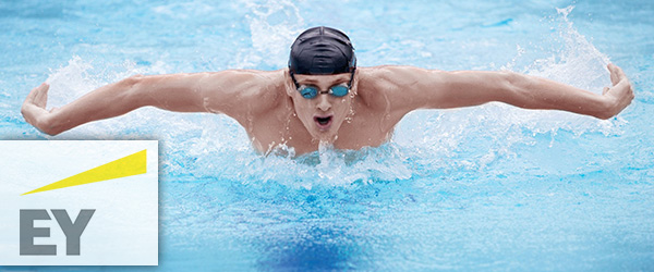 Swimmer in cap and goggles breathing performing the butterfly stroke